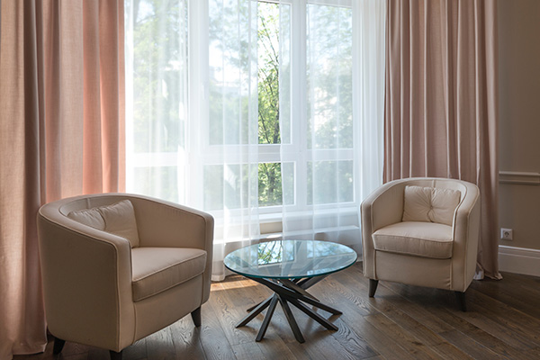 Pastel pink and sheer curtains in seating area