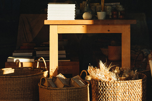 Three wicker baskets under natural wooden table