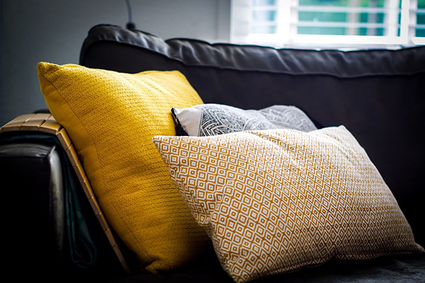 Yellow and patterned cushions on sofa